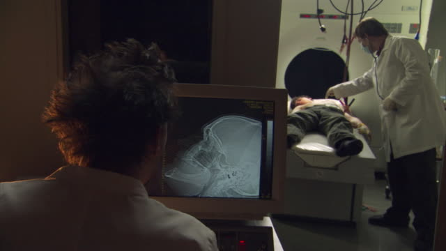 MD Doctor examining scans of human skull on monitor while other medical stuff poking unconscious patient lying on hospital gurney in background / Burlington, Vermont, USA