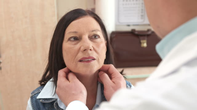 hd: doctor examining senior woman's neck - lymphatic system stock videos & royalty-free footage