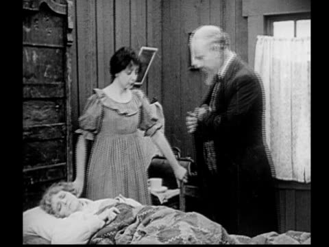 vidéos et rushes de 1915 b/w ms doctor examining sick woman (fanny midgley) lying in bed as younger woman (enid markey) watches / usa - homme dans un groupe de femmes