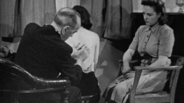 1943 MONTAGE Doctor examining sitting patient's exposed back for lung ailment, and then directing his attention to her coughing sister / United Kingdom