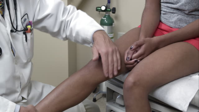 Doctor examining young woman's knee.