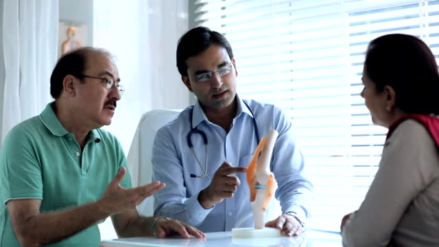Doctor explaining about knee pain to patient, Delhi, India