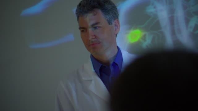 CU ZI Doctor explaining animated model projected on screen / Rockford, Illinois, USA