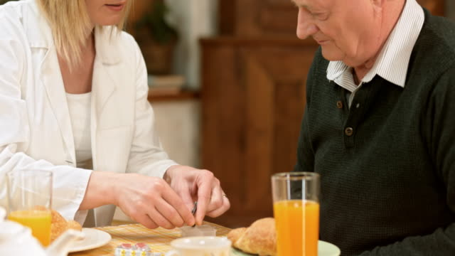 PAN doctor explaining pill usage to senior man at breakfast