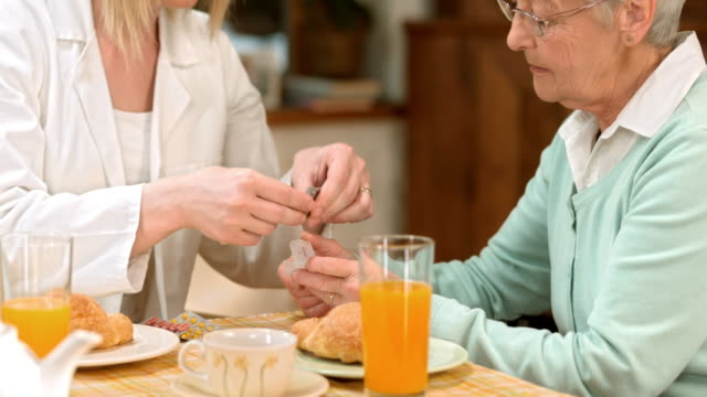 PAN doctor explaining pill usage to senior woman at breakfast