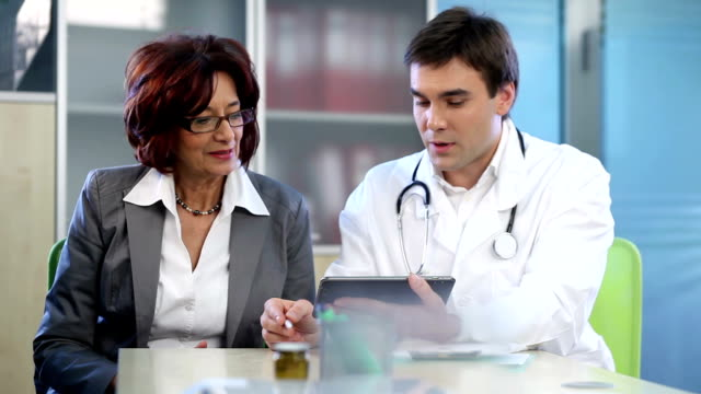 Doctor explaining something to senior woman on digital tablet.