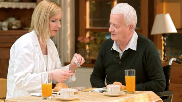Doctor explaining the pill usage protocol to senior man