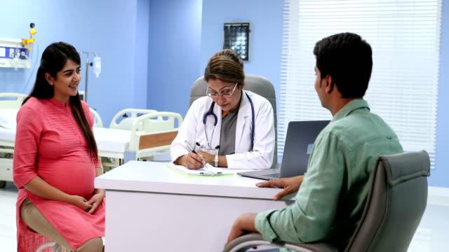 Doctor explaining to couple in hospital, Delhi, India
