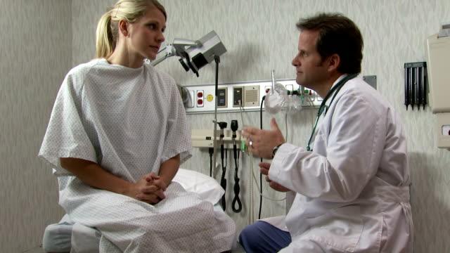 doctor explaining to female patient at medical consultation - untersuchungskittel stock-videos und b-roll-filmmaterial