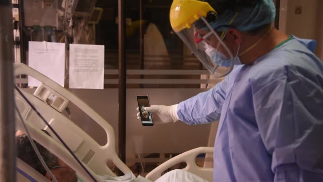 doctor fabian rodriguez wearing personal protective equipment makes a video conference with his cell phone between a patient with covid-19 and his... - colombia stock videos & royalty-free footage