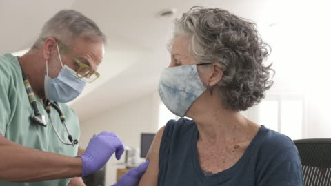 doctor giving a senior woman a vaccination - prevention stock videos & royalty-free footage