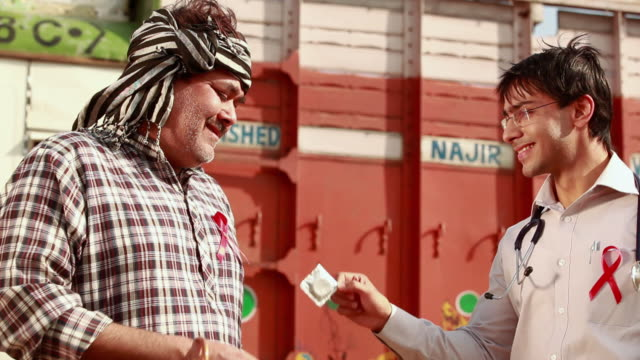 Doctor giving condom to a truck driver, Ballabgarh, Haryana, India