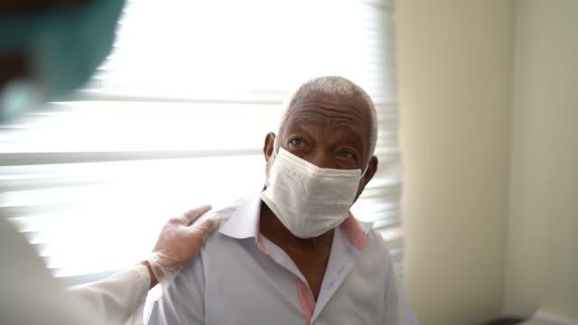 vídeos y material grabado en eventos de stock de médico dando apoyo emocional a un paciente senior usando mascarilla facial - healthcare and medicine