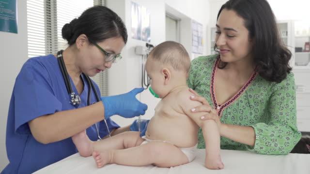 vídeos de stock e filmes b-roll de doctor giving infant a vaccination - social worker