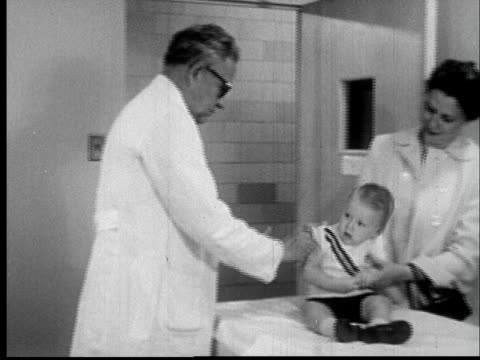 1955 FILM MONTAGE MS doctor giving infant vaccine as mother stands by and watches/ CU Doctor rubbing baby's arm with cotton ball/ AUDIO