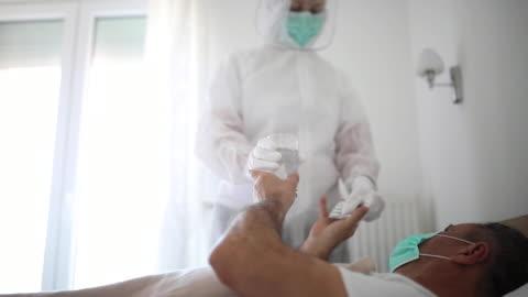 vídeos y material grabado en eventos de stock de médico que da medicamentos a un anciano acostado en la cama del hospital debido a una infección por coronavirus - paciente