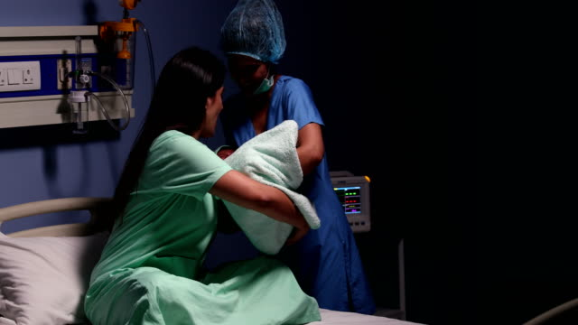 Doctor giving newborn baby to his mother in hospital, Delhi, India