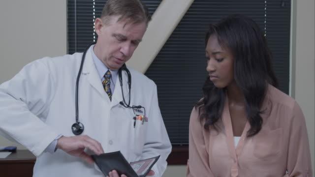 Doctor giving patient's mother a prescription.