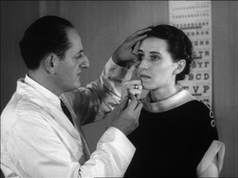 B/W 1936 doctor giving woman eye exam to fit her for contact lenses / newsreel