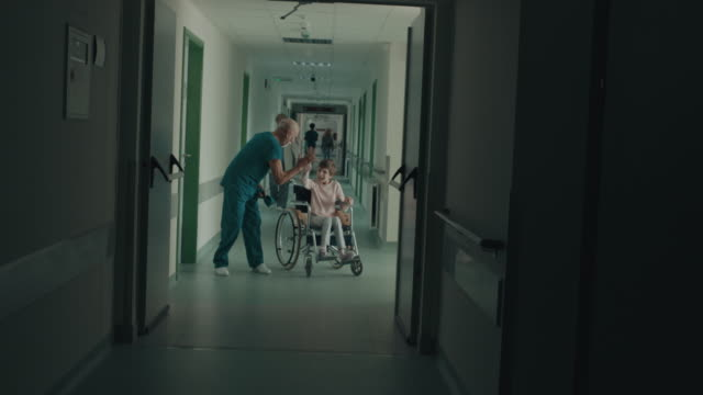 doctor greeting girl in wheelchair with high five - scrubs stock videos & royalty-free footage