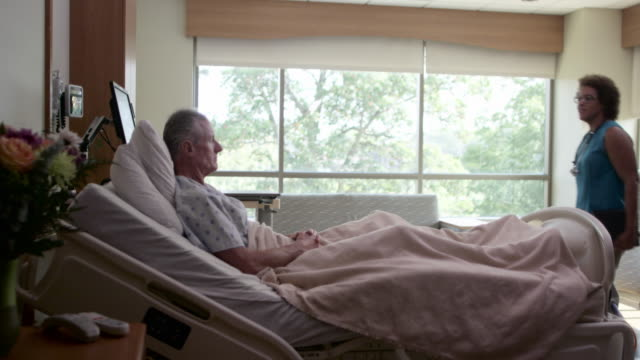 doctor greeting patient in hospital bed - weitwinkelaufnahme stock-videos und b-roll-filmmaterial