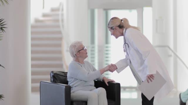vidéos et rushes de doctor greeting patient in waiting room - salle attente