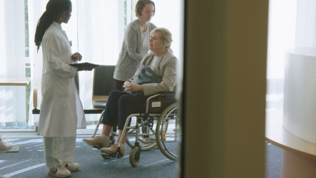 doctor greeting senior disabled patient with family - visit stock videos & royalty-free footage