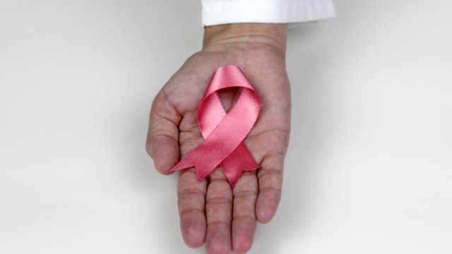 doctor hand holding a pink breast cancer awareness ribbon - societal symbol stock videos & royalty-free footage