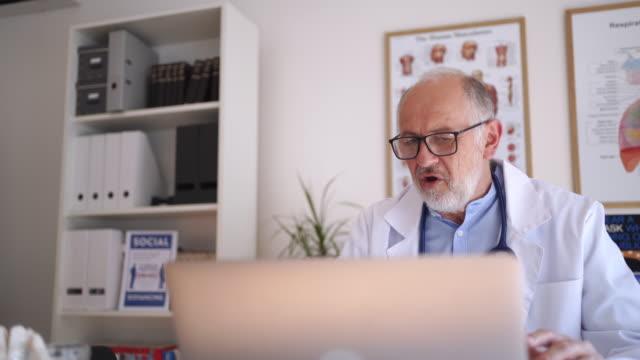 vídeos de stock, filmes e b-roll de médico tem chamada de vídeo à distância com paciente durante o distanciamento social - doutor