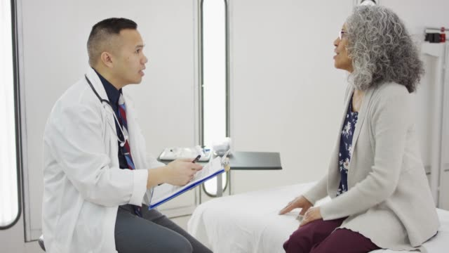 doctor having lively conversation with senior-age patient - pacific islander doctor stock videos & royalty-free footage
