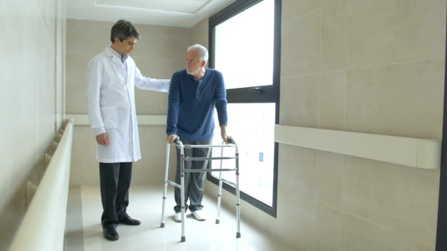 Doctor helping senior man in using mobility walker