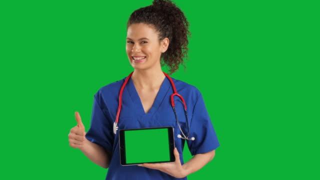 vidéos et rushes de docteur retenant la tablette numérique sur le fond vert d'écran de clef de chroma, pouces vers le haut, mouvement lent - touche de couleur