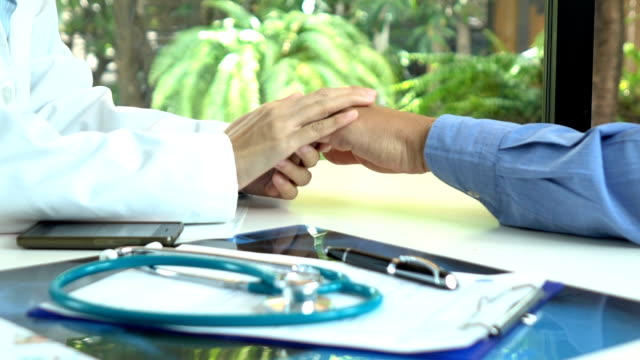 Doctor holding hand to hope with her patient, Healthcare and Medical Concept