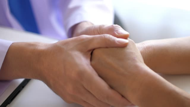 doctor holding patient hands for encouragement , slow motion - holding hands stock videos & royalty-free footage