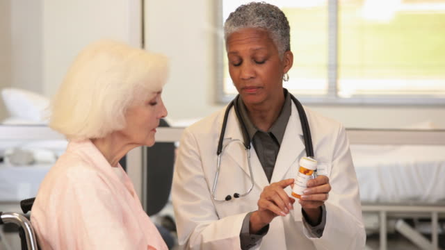 ms tu doctor holding pill bottle, talking to senior patient in wheelchair / richmond, virginia, usa - prescription medicine stock-videos und b-roll-filmmaterial