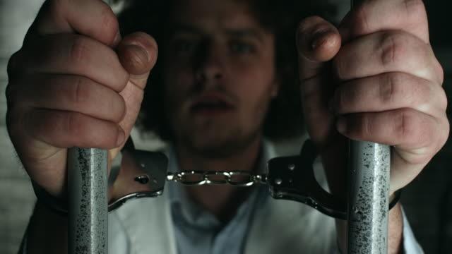 vídeos de stock, filmes e b-roll de doutor, segurando barras de prisão em cela de prisão - mãos juntas