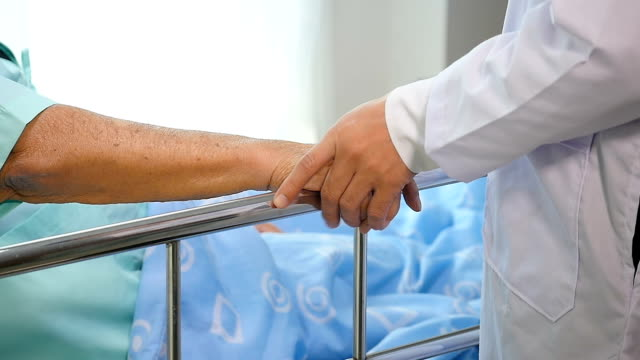 doctor holding senior patient's hands in bed at hospital room, health care and people concept - alzheimer's disease stock videos & royalty-free footage