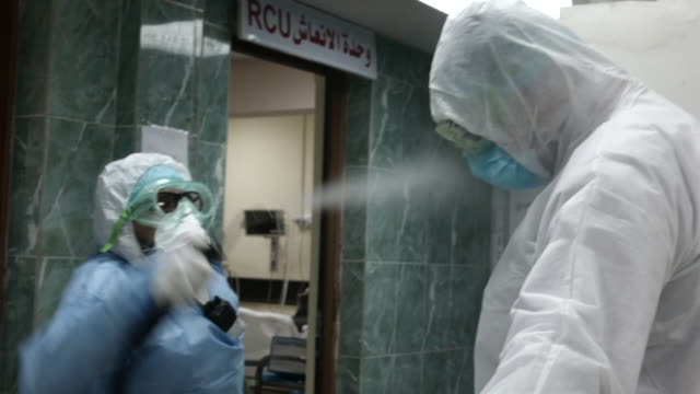 doctor in a baghdad hospital being disinfected whilst wearing ppe during the coronavirus crisis - spray stock videos & royalty-free footage
