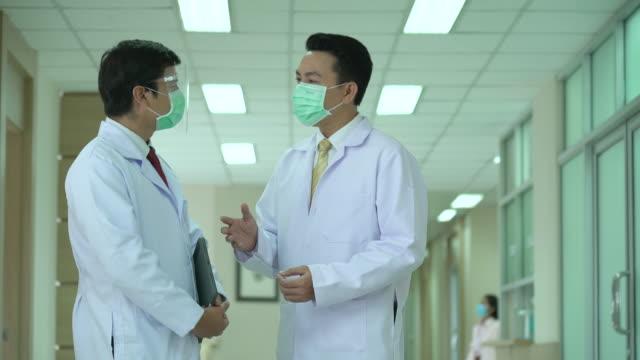 stockvideo's en b-roll-footage met arts in een gesprek met specialist - mid volwassen mannen