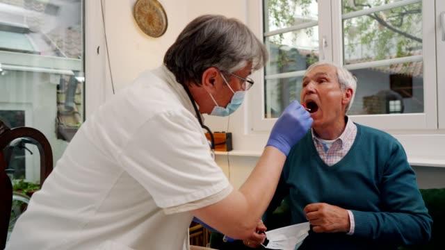 vídeos y material grabado en eventos de stock de médico en una visita a casa a un hombre de la tercera edad - médico de cabecera