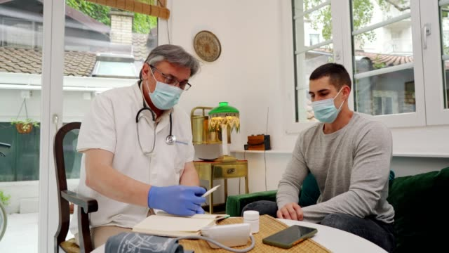 doctor in a home visit to a young man - general practitioner stock videos & royalty-free footage