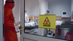 Doctor in an Orange Protective Suit Enters Isolation Room with a Sign Reading Biohazard n the Door - Close Up