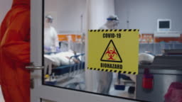 Doctor in an Orange Protective Suit Enters Isolation Room with Coronavirus Patients - Close Up
