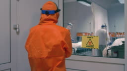 Doctor in an Orange Protective Suit Enters Isolation Room with Coronavirus Patients - Handheld Medium Tracking Shot