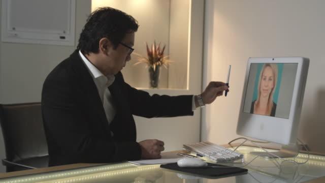 vídeos de stock, filmes e b-roll de ms, doctor in office examining patient's facial symmetry on computer screen, sydney, australia - cirurgia plástica