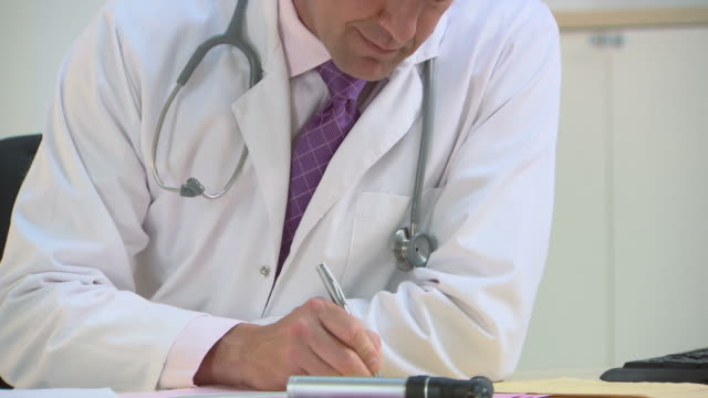 Doctor in office writing prescription, looking up and smiling at camera