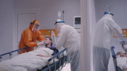 Doctor in Protective Suit Putting on Oxygen Mask on Patient Suffering from Coronavirus - Wide Dolly Shot
