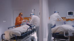 Doctor in Protective Suit Putting on Oxygen Mask on Patient Suffering from Coronavirus - Wide Slow Motion Dolly Shot