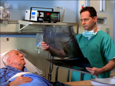 Doctor in scrubs looking at x-rays with senior patient in hospital bed
