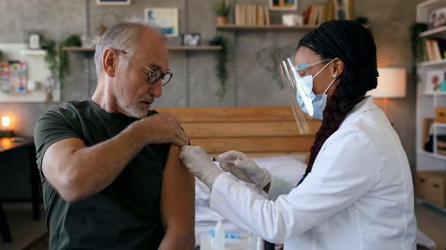 stockvideo's en b-roll-footage met arts die griepvaccin in de wapen van de patiënt injecteert - tekstveld